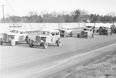 Harvey Jones (6) and Sam McQuagg (90) lead the pack down the backstretch at the Thunderbowl Speedway.  Behind them are Hulon Jones (90), Hulon Jones (second number 6), Willie McDonald (91), as well as Frank Taylor and Earl Powell.  Photo courtesy Earl Powell