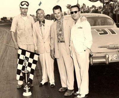 Tim Flock after winning at West Palm Beach.  Pictured third from the left is track promoter Carl Queen.  Note the Georgia dealer tag on Tim's Hudson.  Photo courtesy the Marilynn Clinard collection